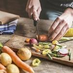 Hände schneiden Gemüse auf Schneidebrett