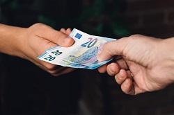 Jemand übergibt zwei Zwanzig-Euro-Scheine