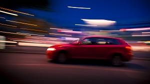 Ein roter Audi A3 fährt bei Nacht vorbei