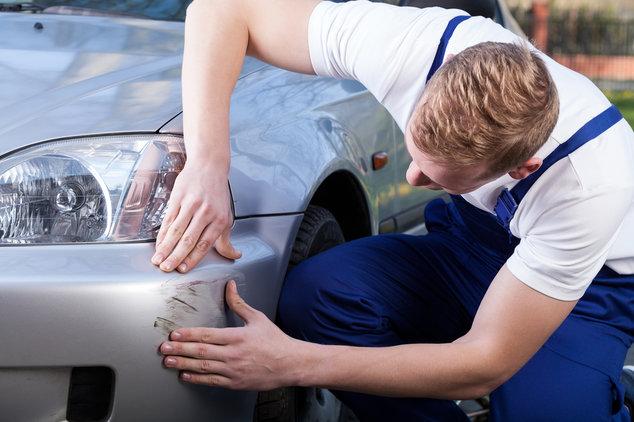 Automechaniker untersucht Schaden an Autofront