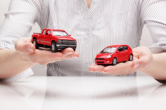 Zwei Spielzeugautos in den Händen einer Frau