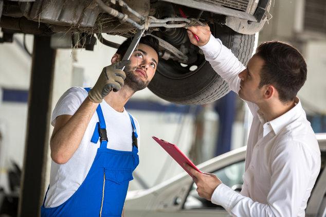 Ein Mechaniker und ein Inspekteur untersuchen einen Wagen, um den Autowert zu berechnen.