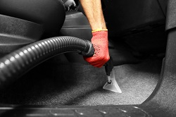 Der Fußraum des Autos wird gesaugt