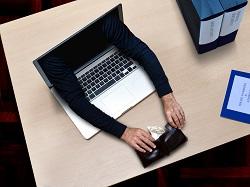 Arme eines Diebs greifen aus dem Computer nach einem Portemonnaie