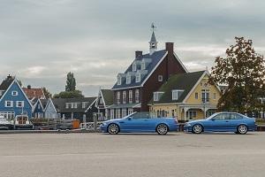 Zwei blaue 3er BMW, davon eins ein Cabriolet, stehen an einem kleinen Hafen in den Niederlanden