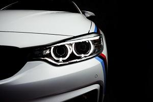 Scheinwerfer eines BMW M Sport mit der charakteristischen Farbbanderole aus Hell- und Dunkelblau sowie Rot