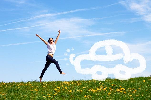 Eine junge Frau hüpft glücklich über eine grüne Wiese vor blauem Himmel, vor dem eine Wolke in Form eines Autos zu sehen ist