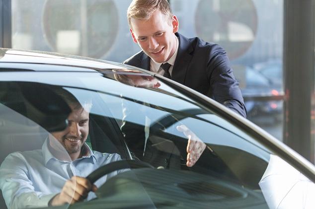 Eine Mann sitzt kurz vor der Probefahrt erfreut in seinem potenziellen neuen Auto, während der Verkäufer die Funktionen erläutert.
