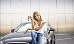 Eine Frau sitzt stolz auf der Motorhaube ihres Jahreswagens