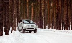 Ein SUV auf dem Weg durch einen verschneiten Wald