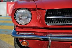 Detailansicht der Front eines älteren roten Ford Mustang, auf der die rechte Front von vorn zu sehen ist