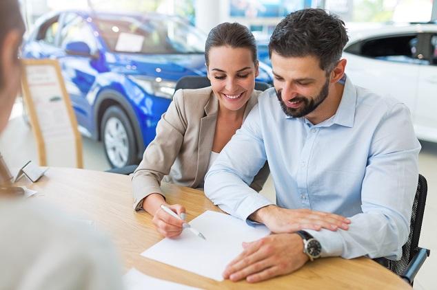Paar unterschreibt Vertrag für Gebrauchtwagen-Leasing