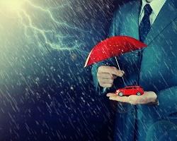 Ein Mann im Anzug hält einen roten Regenschirm zum Schutz vor Blitz und Gewitter über ein kleines rotes Modellauto in seiner Hand