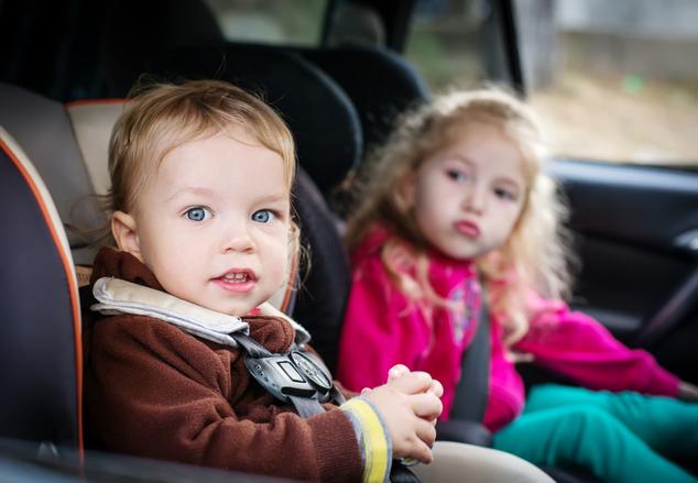 Zwei Kinder in Kindersitzen im Auto