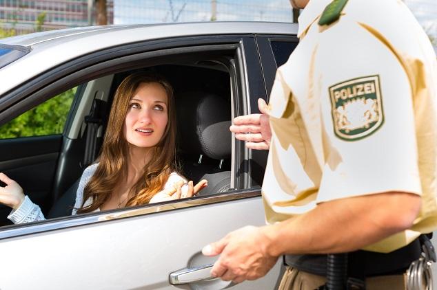 Frau im Auto wird von Polizei befragt