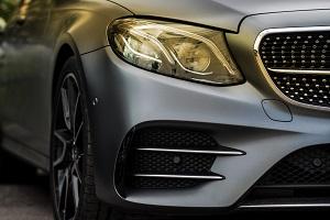 Detailansicht der Front eines Mercedes-Benz mit Scheinwerfer, Teil des Kühlergrills und vorderem Kotflügel