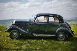 Seitenansicht eines schwarzen Mercedes-Benz Oldtimers auf einer grünen Wiese