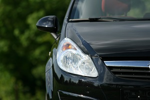 Detailansicht eines schwarzen Opel Corsa mit Frontscheinwerfer und Teil des Kühlergrills