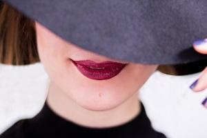 Junge Frau verdeckt ihr Gesicht mit ihrem Hut