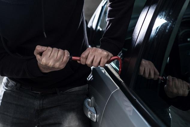Ein Dieb bricht ein Auto auf