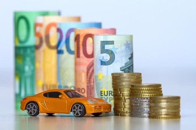 Oranges Modellauto vor Geldscheinen und Münzen der Währung Euro
