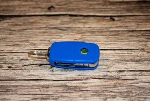 Ein blauer Autoschlüssel mit Skoda-Logo liegt auf einem hölzernen Untergrund