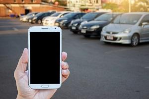 Ein Mann hält ein Smartphone hoch, dahinter ist ein Parkplatz mit Autos zu sehen