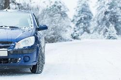 Ein blaues Winterauto im Schnee