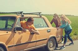 Junge Menschen schieben ein altes Auto an