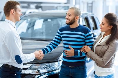Ein Verkäufer begrüßt Kunden in einem Autohaus.